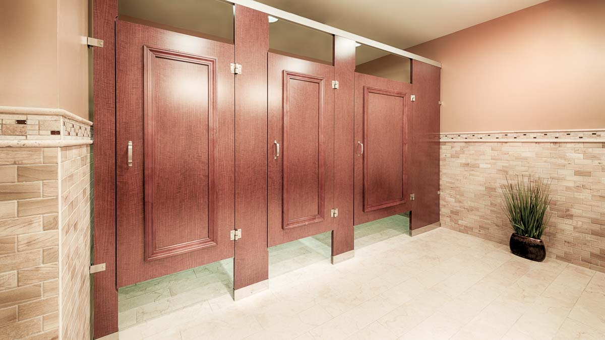 Three between wall wood grain laminate bathroom partitions and doors accented with picture frame molding stained to match laminate.
