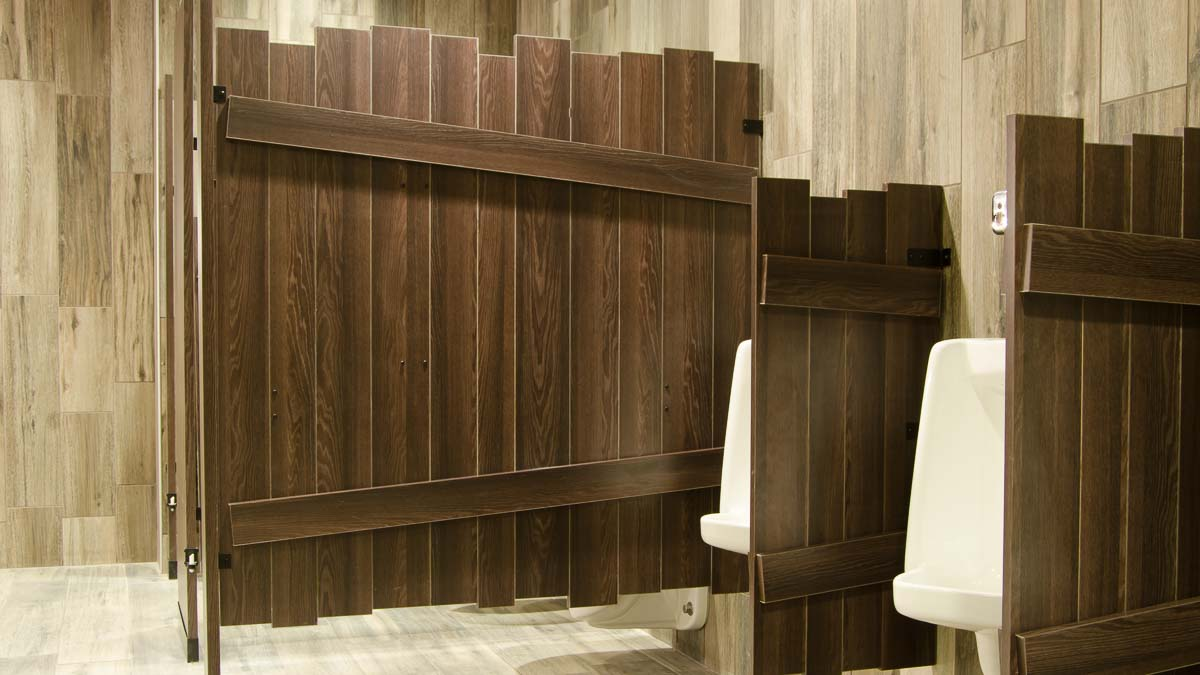 Custom shape laminate bathroom partitions with purposeful uneven edges on brown, outhouse look compartment and privacy screen between urinals.