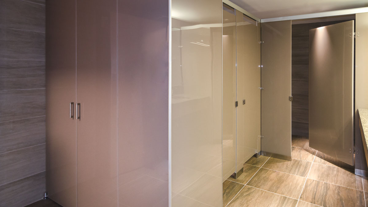 Reflective tan colored, high gloss Zenolite application on oversize all gender bathroom partitions in swanky office environment.