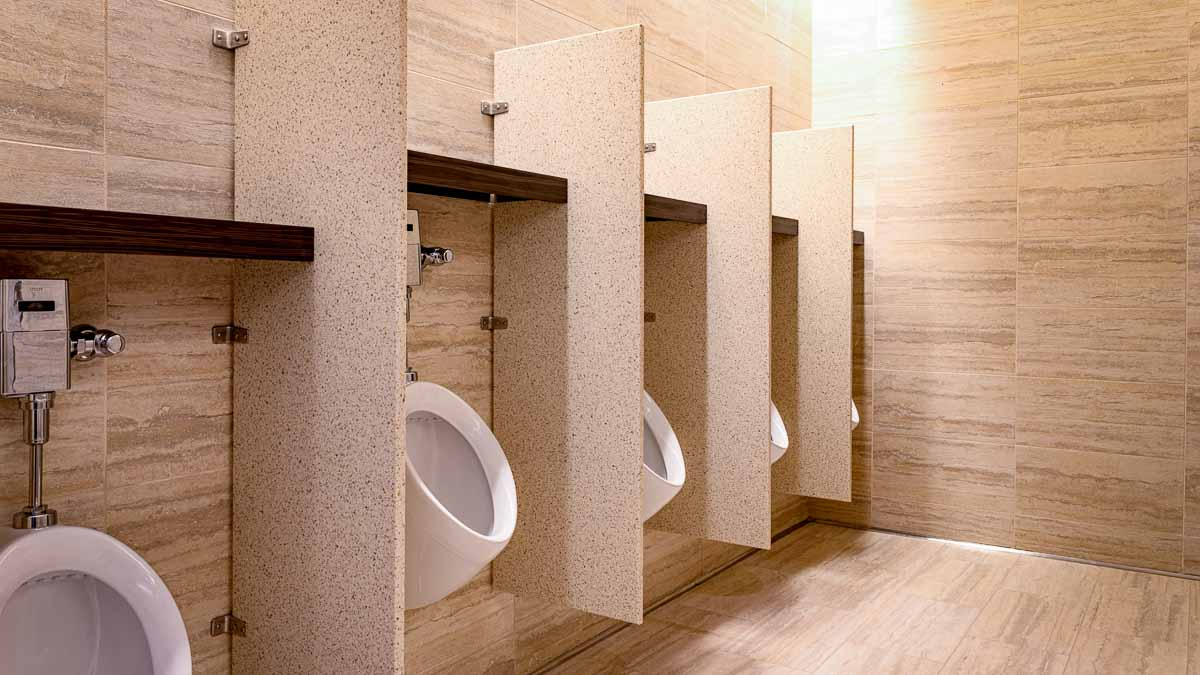 Upscale men's casino bathroom in neutral tans showcasing four, wall mounted solid surface urinal privacy screens with laminate shelf above urinals.