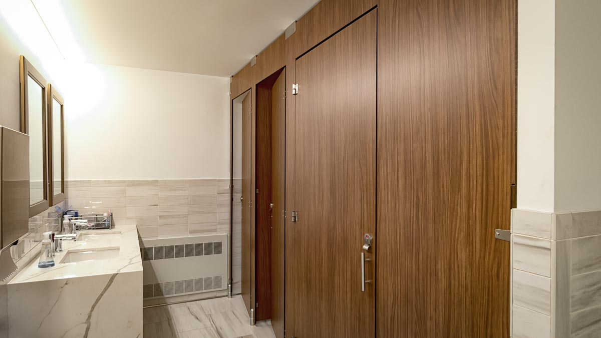 Top of the line employee bathroom in compact laminate partitions with oversize configuration showing transoms for added privacy.
