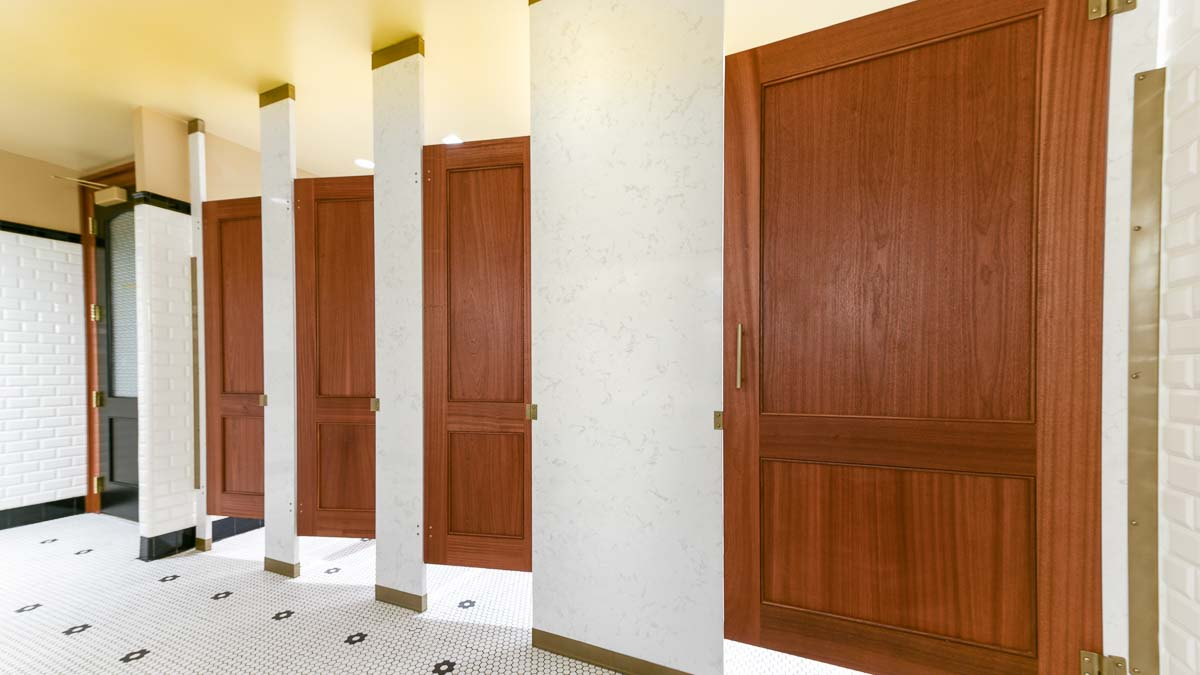 Classy business headquarters tiled bathroom features engineered stone pilasters with four wood veneer, captured panel doors with bronzed hardware.