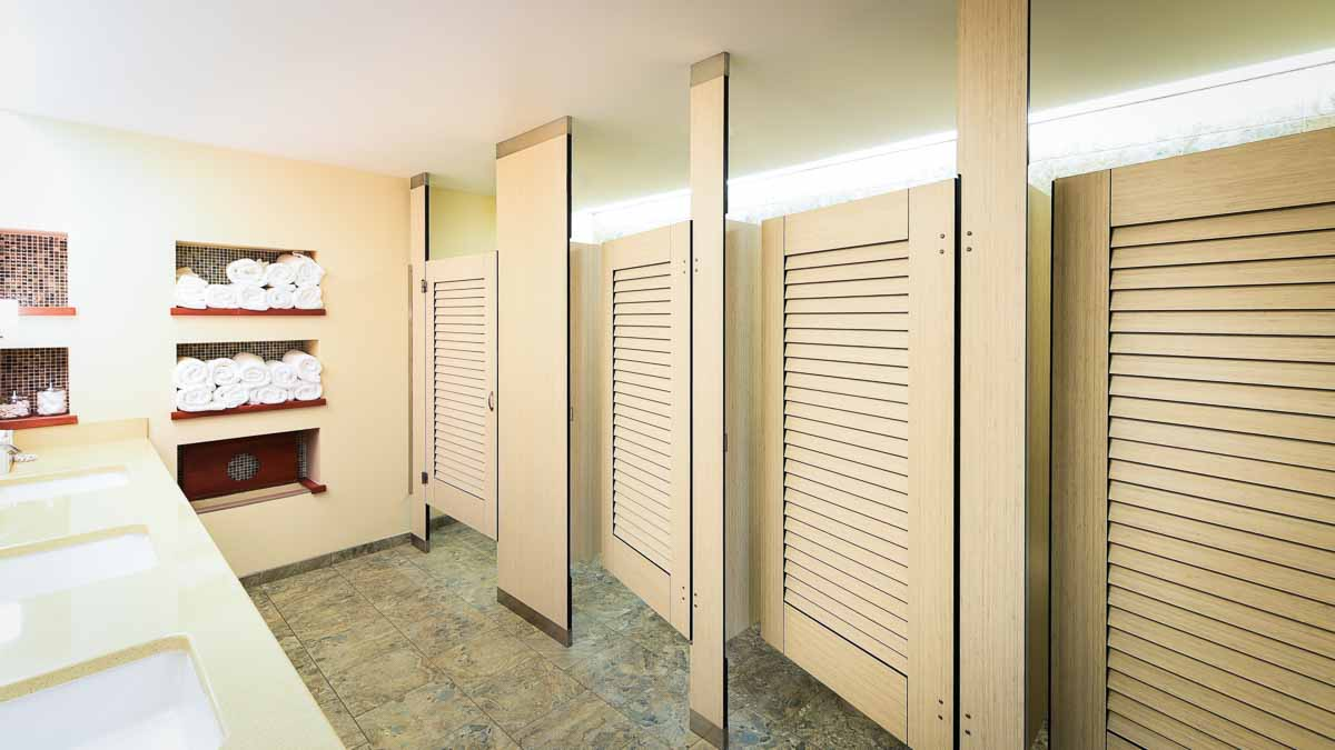 Bright Country Club locker room features off-white, compact laminate partitions and louver doors in floor to ceiling style. Rolled towels on shelf.