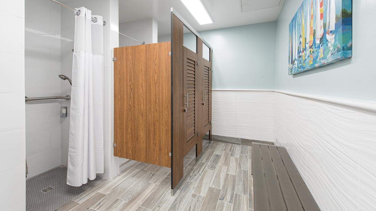 Yacht Club features compact laminate, wood grain dressing compartments with two louver doors. Sailboat print on wall above grey metal changing bench.