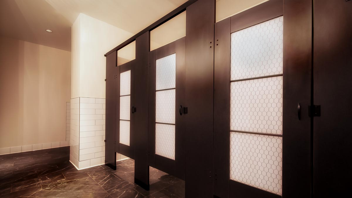 Unique hotel bathroom with black laminate partitions, powder coat hardware and chicken wire design on acrylic door lite inserts.
