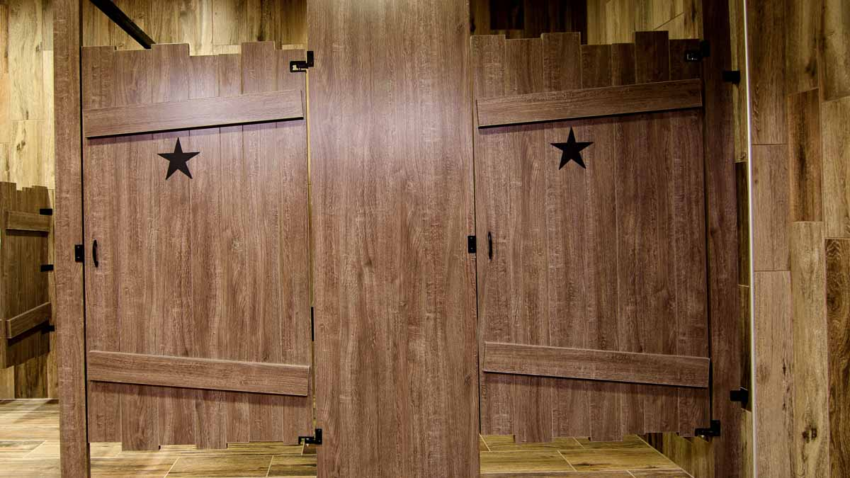 Two custom shape, brown laminate bathroom compartments with purposeful uneven top and bottom edges on outhouse look with star engraving on each door.
