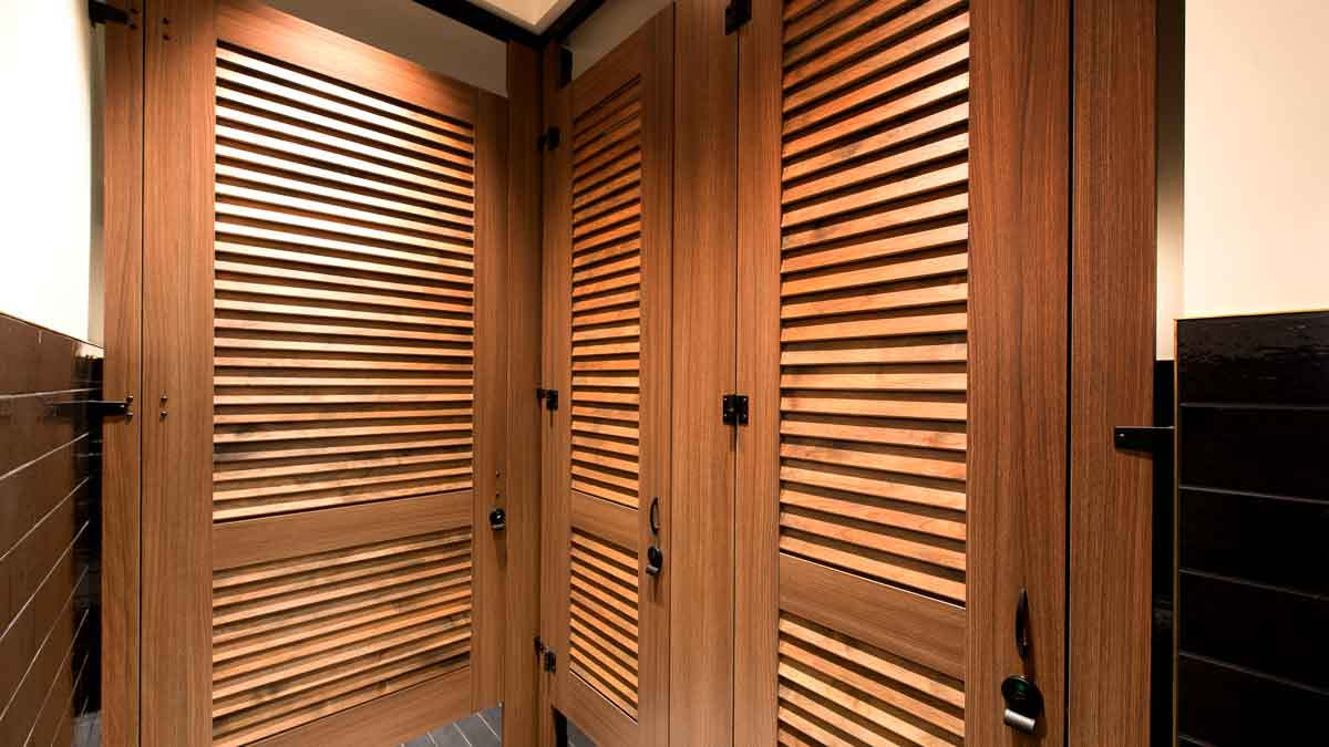 Trendy hotel bathroom showing full height, zero sightline, wood grain laminate partitions with three louver doors with black powder coat hardware.