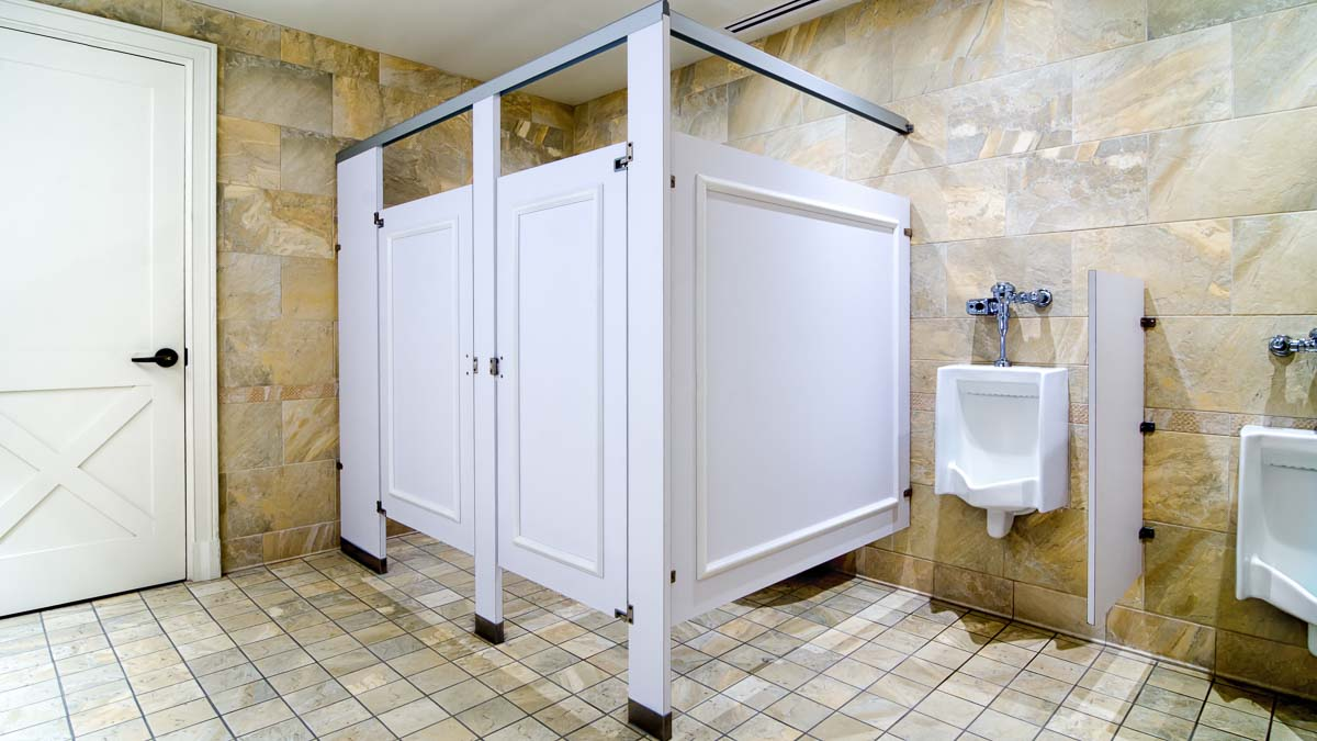 Elegant tan marbled men's bathroom featuring white laminate standard size partition accentuating picture frame molding on door and panels.