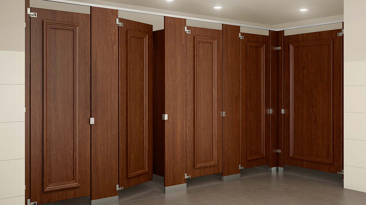 Full height wood grain laminate bathroom partitions and four doors with accenting picture frame molding stained to match laminate.