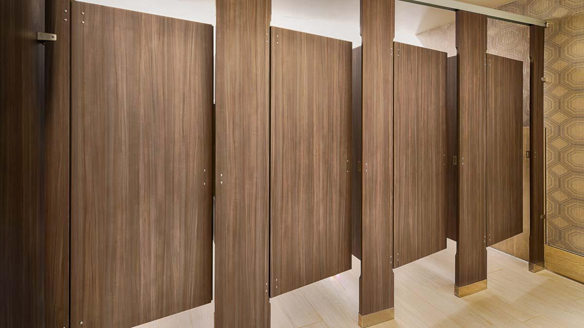 Four brown laminate, standard size bathroom partitions. Open doors spotlighting zero sightline view of overlapping doors and pilasters.
