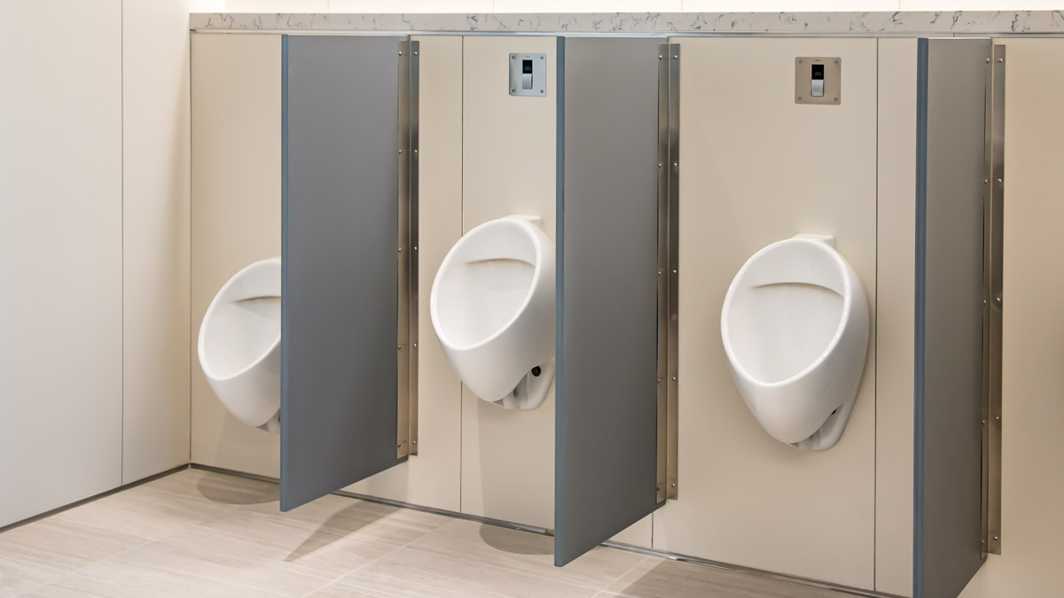 Three modern urinal screens in grey solid surface material showing a wall mounted continuous bracket in men's bathroom.