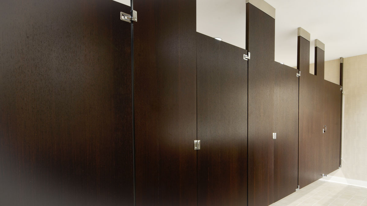 Elegant hotel bathroom featuring multiple, rich brown wood veneer partitions. Simplistic design creates open feel in ceiling hung configuration.