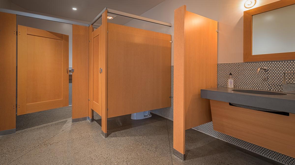 Men's bathroom features two warm honey colored wood veneer captured panel doors with one floor mount privacy urinal screen next to grey stone vanity.