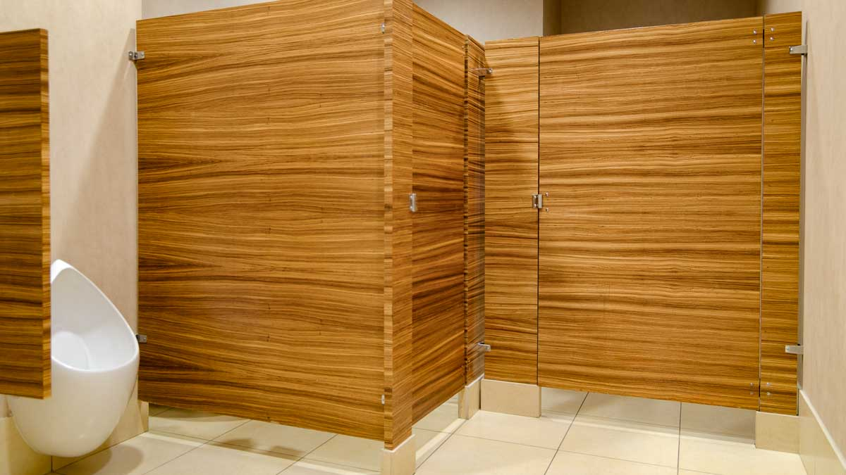 Upscale hotel bathroom with two wood veneer (zebrawood) floor mount corner partitions highlight a rich wood grain presentation.
