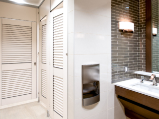 Dealership showroom bathroom with high privacy European style toilet partition shows white laminate louver doors and transoms. Brown tile urban room.