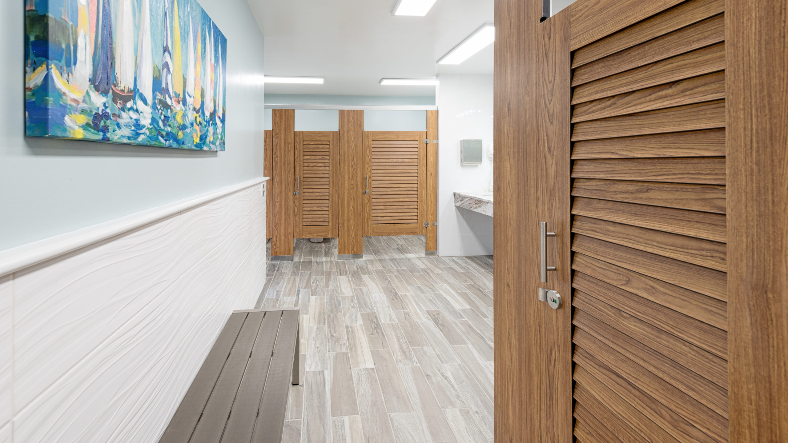 Marina bathroom features compact laminate, wood grain louver doors in headrail braced style. Sailboat print on wall above grey metal changing bench.