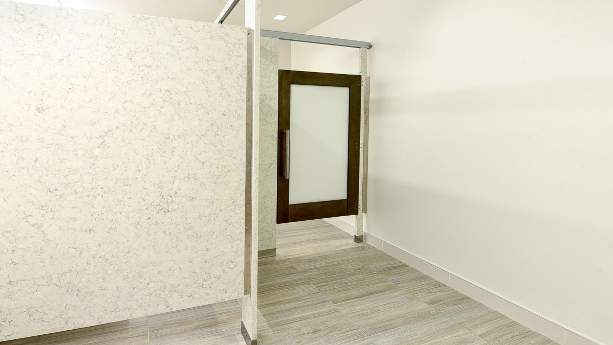 Grey and white marble look engineered stone partitions feature wood veneer door with frosted acrylic door lite insert and eighteen-inch ladder pull.