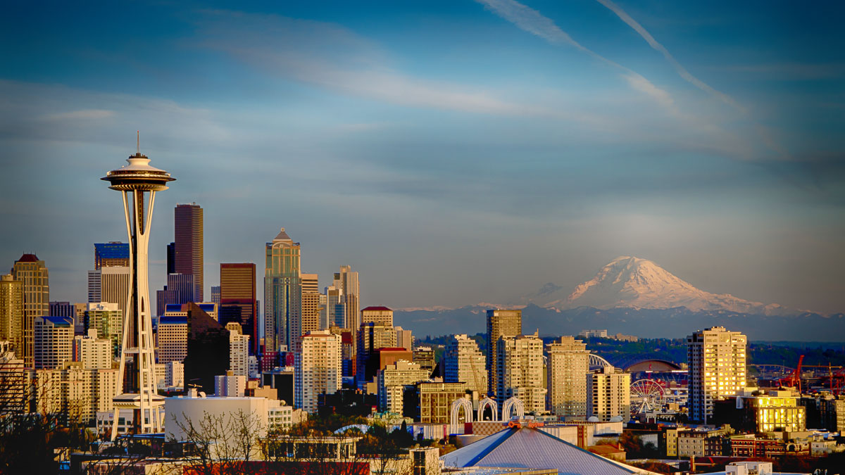 Gorgeous Seattle city skyline featuring the iconic Space Needle and impressive snow-covered Mt. Ranier against a beautiful blue sky.